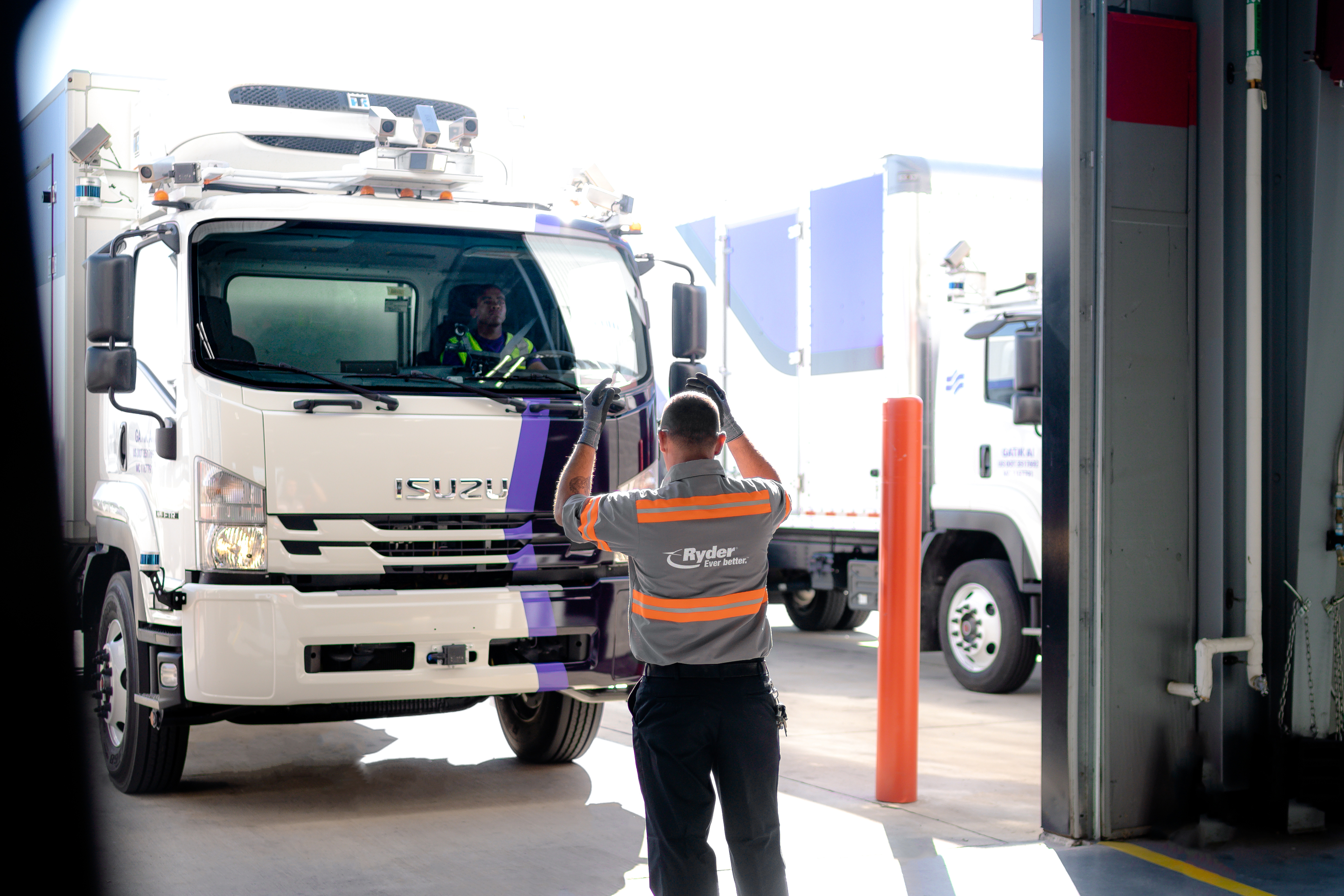 A Ryder technician guides a Gatik autonomous truck with a safety driver behind the wheel into a Ryder maintenance shop near Fort Worth, TX. Ryder has invested in Gatik and will provide leasing and maintenance services for Gatik's fleet of autonomous trucks, with the goal to establish a business-to-business short-haul logistics delivery network across the U.S. and Canada. (Photo: Business Wire)